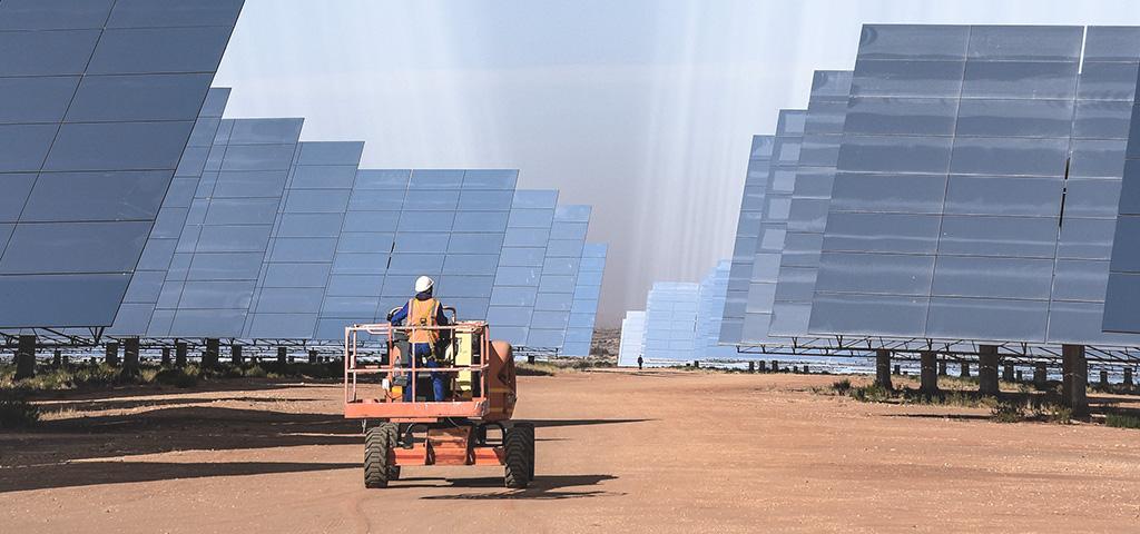 Mann, der in Upington (Südafrika) zwischen Solarmodulen fährt.