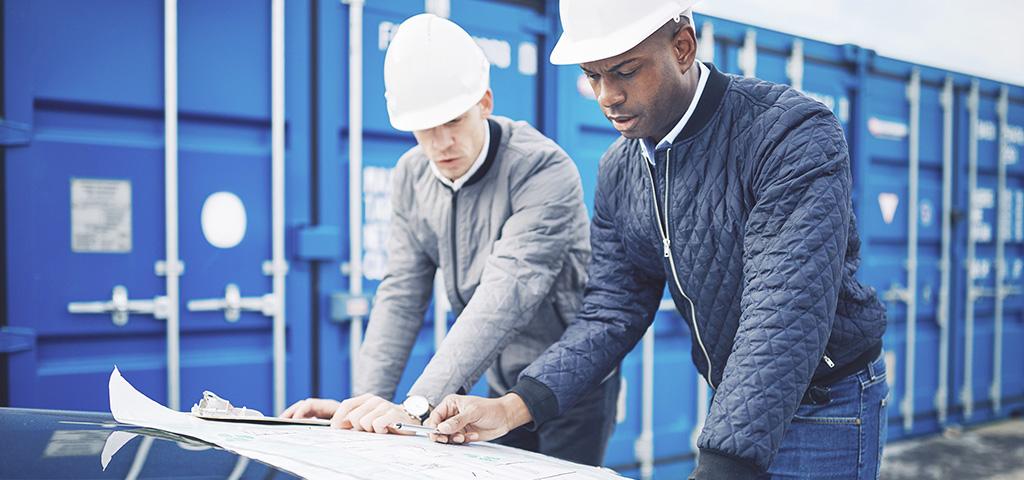 Männer über Bauplänen in Südafrika