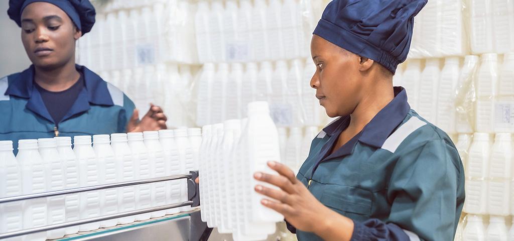 Frauen, die in Nigeria Getränkeflaschen sortieren | Afrika, Wirtschaft, Kunststoffflaschen zur Abfuellung auf das Foederband.
