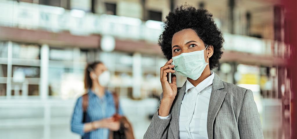 Geschäftsfrau am Flughafen mit Maske während Coronapandemie